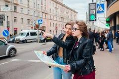 Deux jeunes femmes élégantes voyageant et regardant la carte dans la ville Images libres de droits