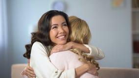 Deux jeunes femmes étreignant et souriant sincèrement, véritable vieille amitié, à l'intérieur clips vidéos