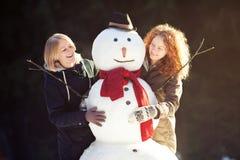 Deux jeunes femmes étreignant le bonhomme de neige Image stock