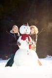 Deux jeunes femmes étreignant le bonhomme de neige Photographie stock libre de droits