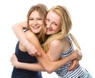 Deux jeunes femmes étreignent en tant que des meilleurs amis Photos stock