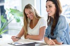 Deux jeunes femmes étudiant des graphiques sur le bureau blanc Photo stock