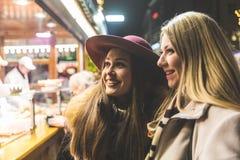 Deux jeunes femmes achetant la nourriture au marché de Noël à Munich Photo stock