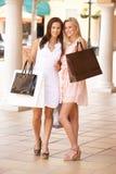 Deux jeunes femmes appréciant des achats Photos stock