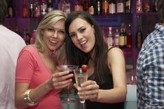Deux jeunes femmes appréciant des boissons dans la barre Photos stock