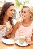 Deux jeunes femmes appréciant la cuvette de café photos stock