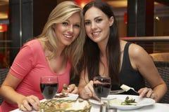 Deux jeunes femmes appréciant le repas dans le restaurant Photo stock