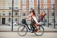 Deux jeunes femmes appréciant le tour de vélo sur la rue de ville Photographie stock libre de droits