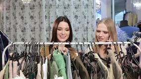 Deux jeunes femmes attirantes choisissant des vêtements dans le magasin clips vidéos