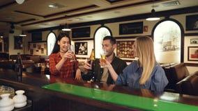 Deux jeunes femmes attirantes et jeune homme barbu boivent de la bière se reposant au compteur, à faire tinter et à parler de bar banque de vidéos