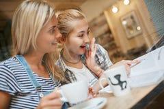 Deux jeunes femmes attirantes lisant le magazine et la séance i de merveille photo stock
