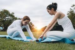Deux jeunes femmes attirantes pliant l'afte bleu de tapis de yoga ou de forme physique photographie stock