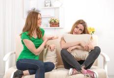 Deux jeunes femmes attirantes s'asseyent sur un sofa dans la chambre et parlent a Image stock
