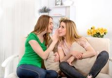 Deux jeunes femmes attirantes s'asseyent sur un sofa dans la chambre et parlent a Photo libre de droits