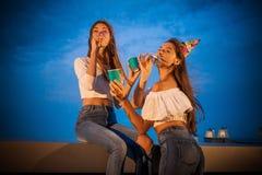 Deux jeunes femmes attirantes saluent et célèbrent l'anniversaire de soufflement de la trompette et soulèvent leurs mains photos stock