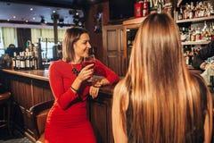 Deux jeunes femmes attirantes se réunissant dans un bar pour le verre de vin rouge se reposant au compteur se souriant Photo libre de droits