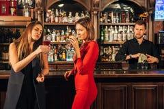 Deux jeunes femmes attirantes se réunissant dans un bar pour le verre de vin rouge se reposant au compteur se souriant Photographie stock