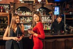 Deux jeunes femmes attirantes se réunissant dans un bar pour le verre de vin rouge se reposant au compteur se souriant Photo stock
