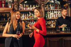 Deux jeunes femmes attirantes se réunissant dans un bar pour le verre de vin rouge se reposant au compteur se souriant Images stock