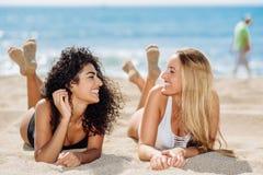Deux jeunes femmes avec de beaux corps dans le maillot de bain sur un tropical Photos stock