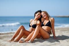 Deux jeunes femmes avec de beaux corps dans les vêtements de bain sur un tropical Photographie stock libre de droits