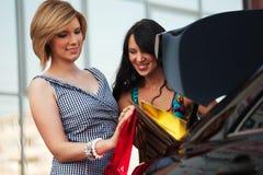 Deux jeunes femmes avec des sacs à provisions. Images stock