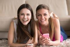 Deux jeunes femmes avec des téléphones portables ayant l'amusement en ligne Image stock