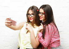 Deux jeunes femmes avec des verres de partie prenant le selfie Photos stock