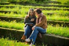Deux jeunes femmes avec du charme s'asseyent aux étapes en pierre avec le comprimé dans des mains Photo libre de droits