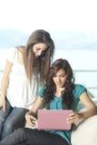 Deux jeunes femmes avec l'ordinateur portatif Image libre de droits