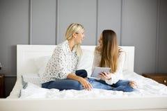 Deux jeunes femmes avec le comprimé sur le lit Photos stock