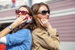 Deux jeunes femmes avec le téléphone portable Photographie stock libre de droits