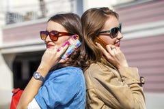Deux jeunes femmes avec le téléphone portable Photos stock
