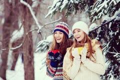 Deux jeunes femmes avec les tasses colorées buvant le thé extérieur et le smil Image stock