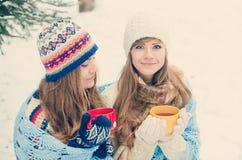 Deux jeunes femmes avec les tasses colorées buvant le thé extérieur et le smil Photo stock