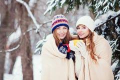 Deux jeunes femmes avec les tasses colorées buvant le thé extérieur et le smil Images libres de droits