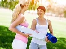 Deux jeunes femmes avec un tapis de gymnase causant en parc Photos stock