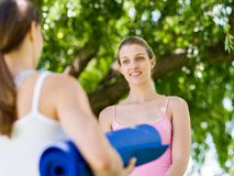 Deux jeunes femmes avec un tapis de gymnase causant en parc Photo libre de droits