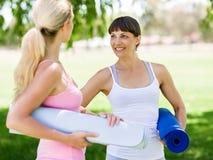 Deux jeunes femmes avec un tapis de gymnase causant en parc Image stock