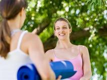 Deux jeunes femmes avec un tapis de gymnase causant en parc Photographie stock