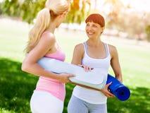 Deux jeunes femmes avec un tapis de gymnase causant en parc Images stock