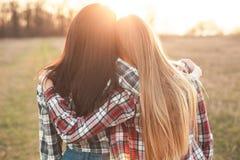 Deux jeunes femmes ayant l'amusement au coucher du soleil Image libre de droits
