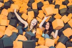 Deux jeunes femmes ayant l'amusement avec des blocs de doux aux enfants d'intérieur p Photos stock