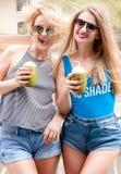 Deux jeunes femmes ayant l'amusement et buvant le cocktail dans le jour d'été Images stock