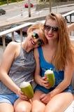 Deux jeunes femmes ayant l'amusement et buvant le cocktail dans le jour d'été Image stock