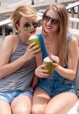 Deux jeunes femmes ayant l'amusement et buvant le cocktail dans le jour d'été Photo libre de droits