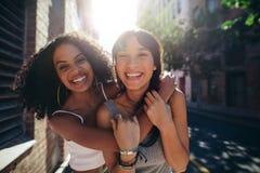 Deux jeunes femmes ayant l'amusement sur la rue de ville Photo libre de droits
