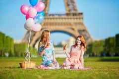 Deux jeunes femmes ayant le pique-nique près de Tour Eiffel à Paris, France Photo stock