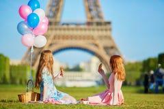 Deux jeunes femmes ayant le pique-nique près de Tour Eiffel à Paris, France Images stock
