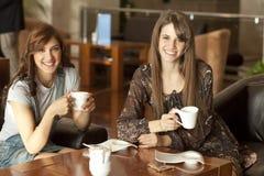 Deux jeunes femmes buvant du café Images stock